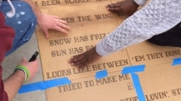 Artists use a stencil to install a temporary poem on the sidewalk in Boston.